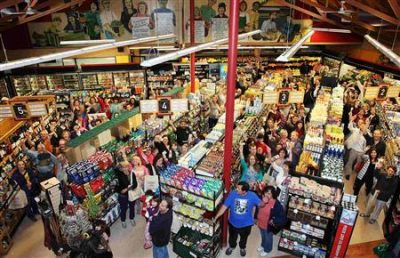 "Customers line the aisles and hold up their money as they participate in a ""cash mob"" at a small locally owned organic store called Nature's Bin, in Lakewood"